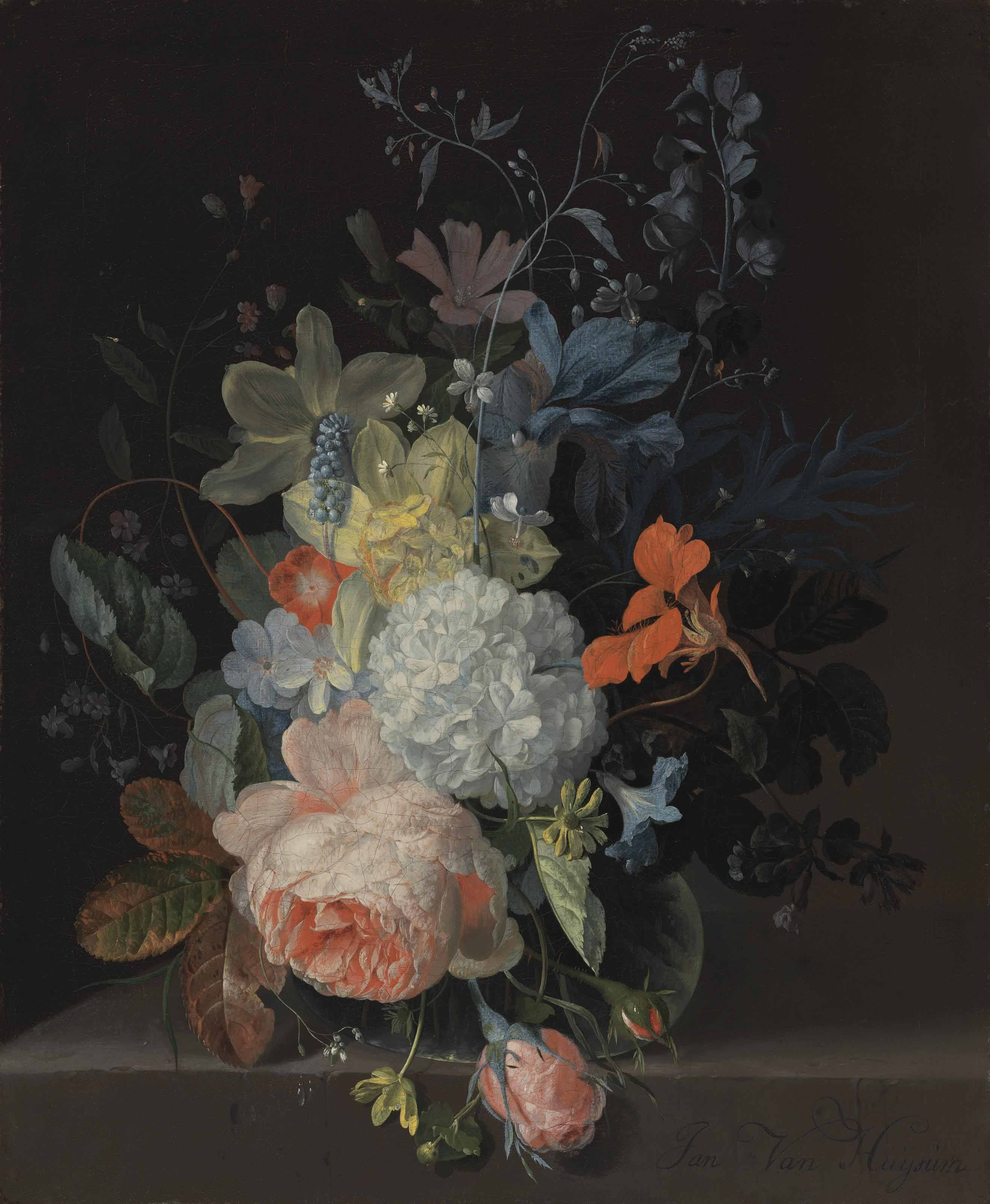 A rose, a snowball, daffodils, irises and other flowers in a glass vase, on a stone ledge