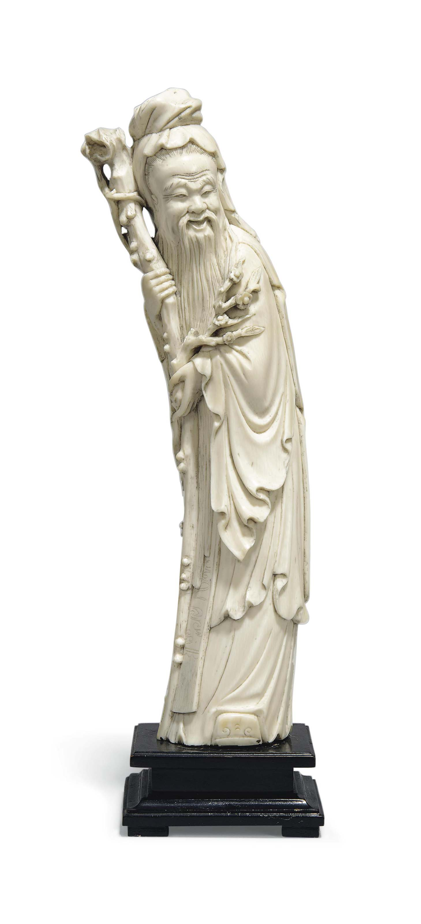 A CARVED IVORY FIGURE OF AN IM