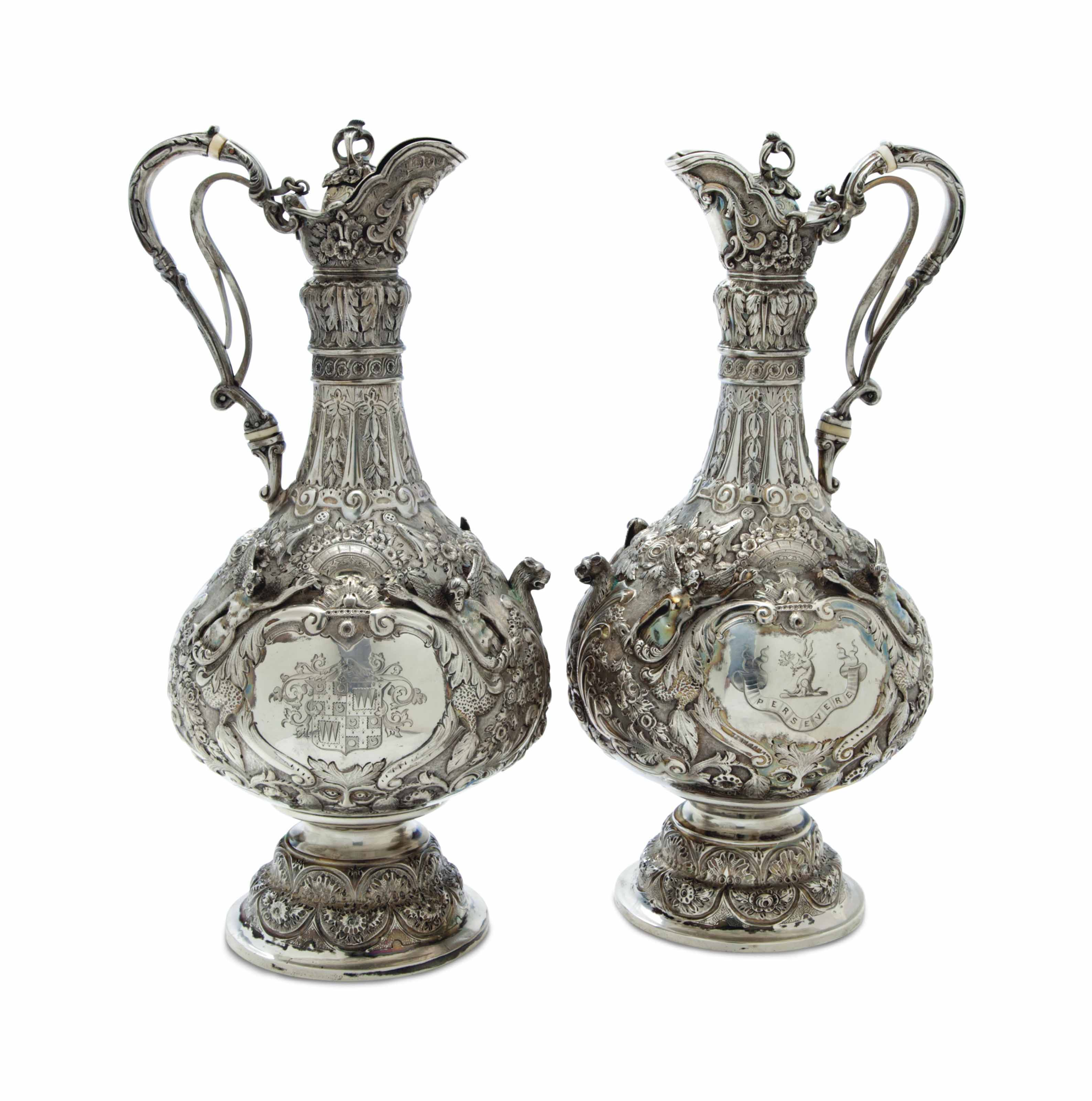 A MATCHED PAIR OF ENGLISH REPOUSSE SILVER EWERS