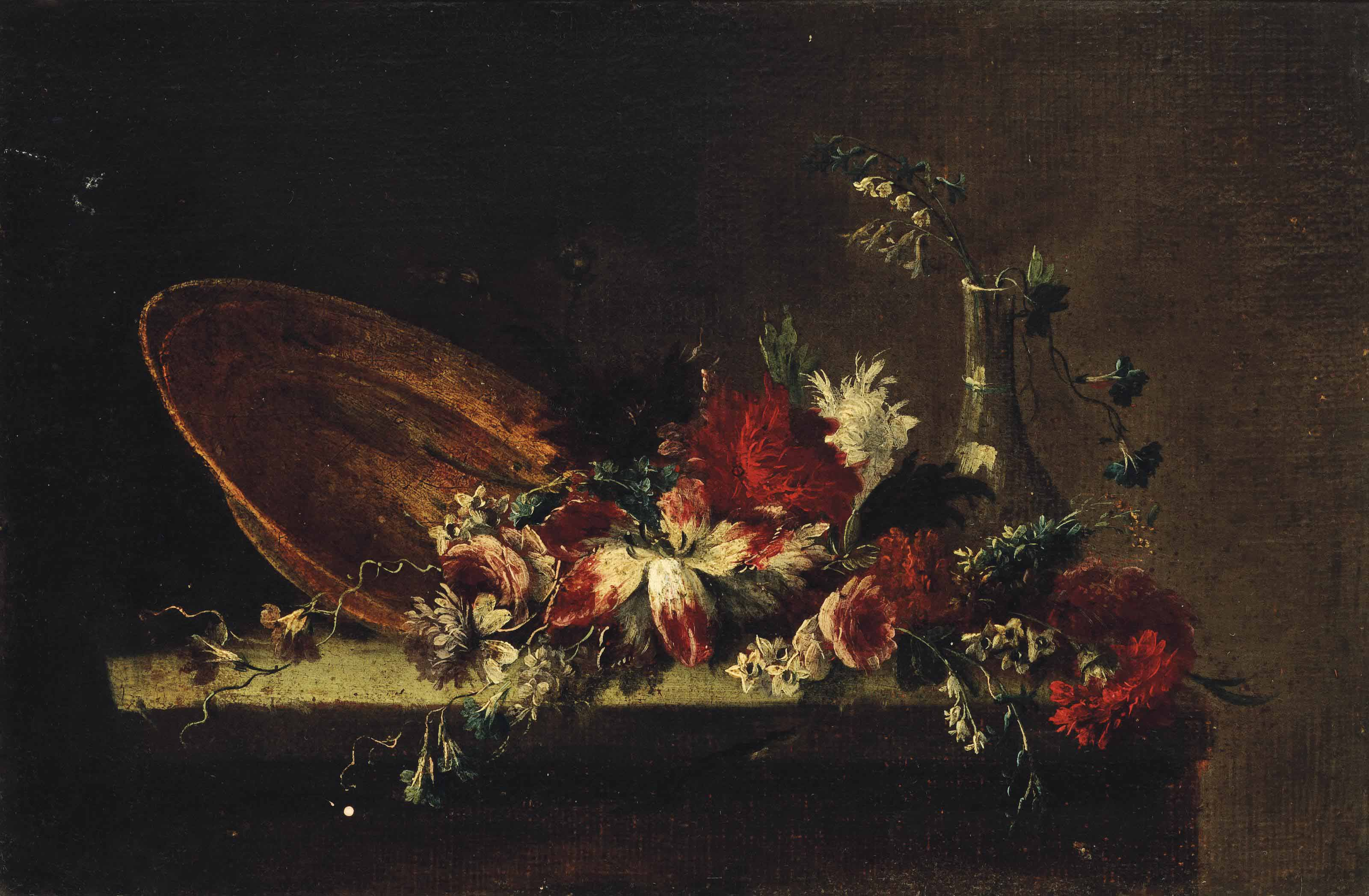 Roses, carnations, narcissi and other flowers with an upturned plate and a glass vase on a stone ledge