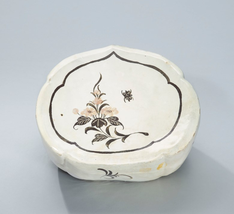 A Henan incised and painted polychrome butterfly ruyi-shaped pillow, Northern Song Dynasty (960-1127). 10⅛  in (25.7  cm) long, box. Sold for HK$212,500 on 4 October 2016  at Christie's in Hong Kong