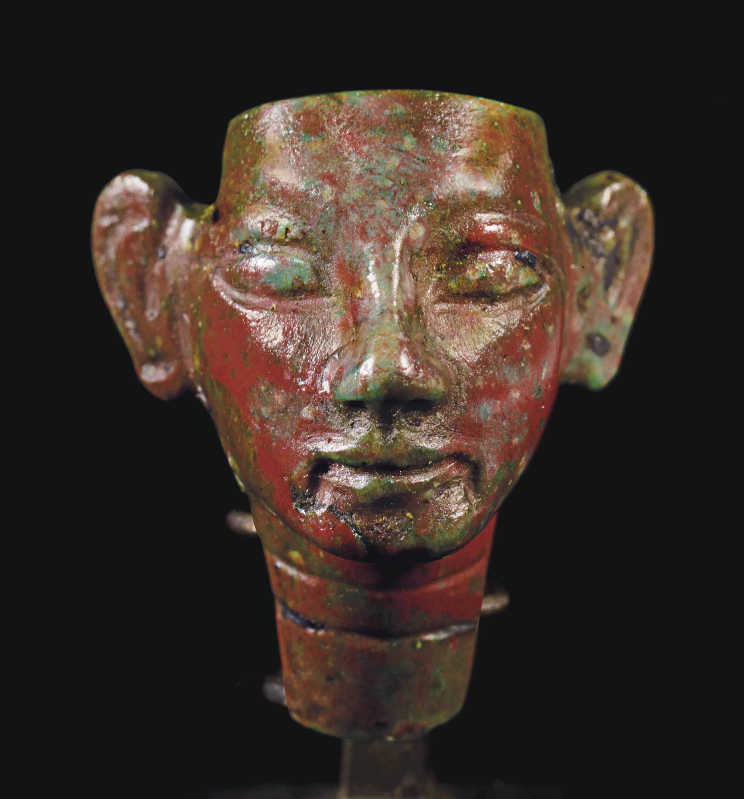 AN EGYPTIAN RED GLASS ROYAL HE