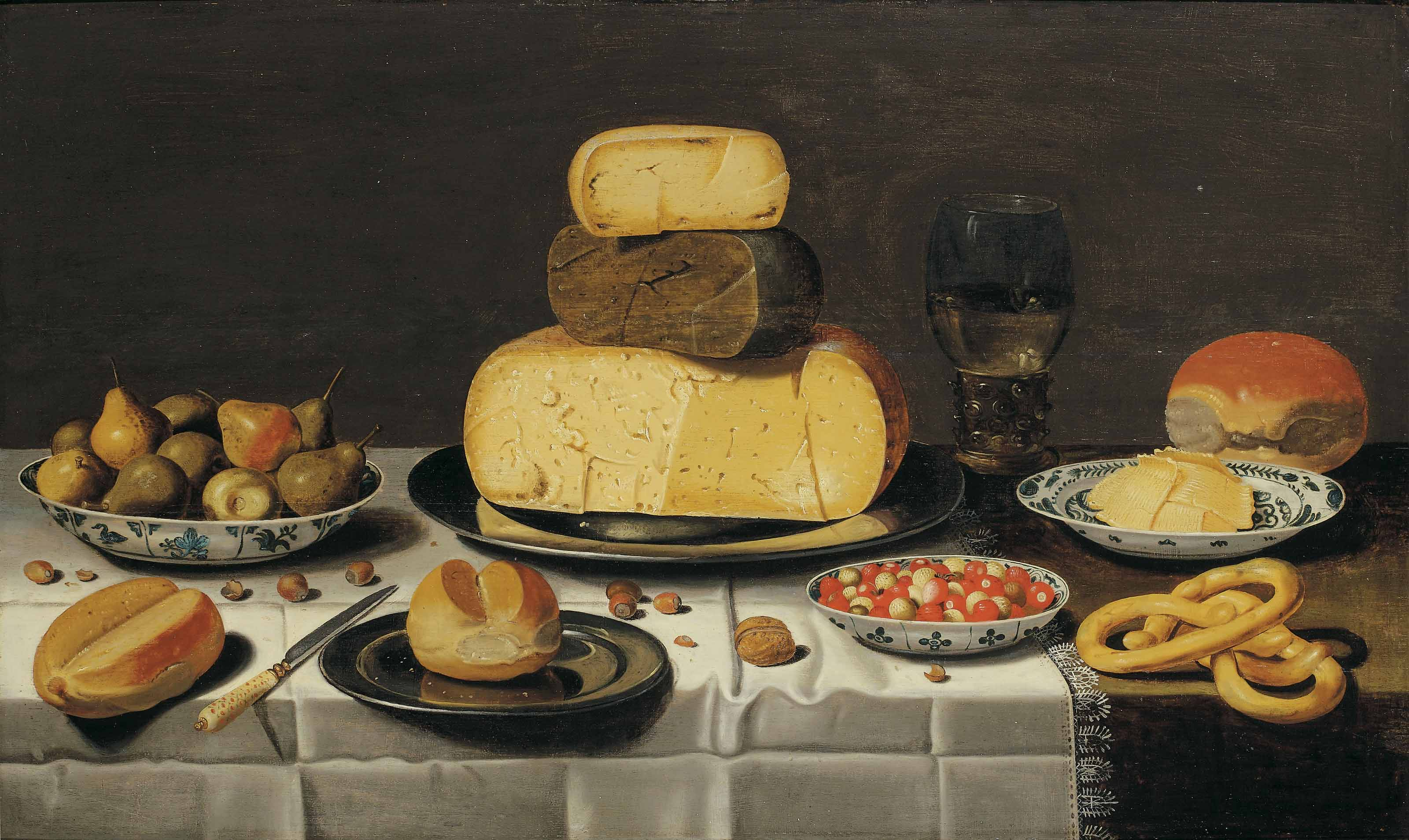 A breakfast piece with cheese, bread, fruit and a roemer, on a partially draped table