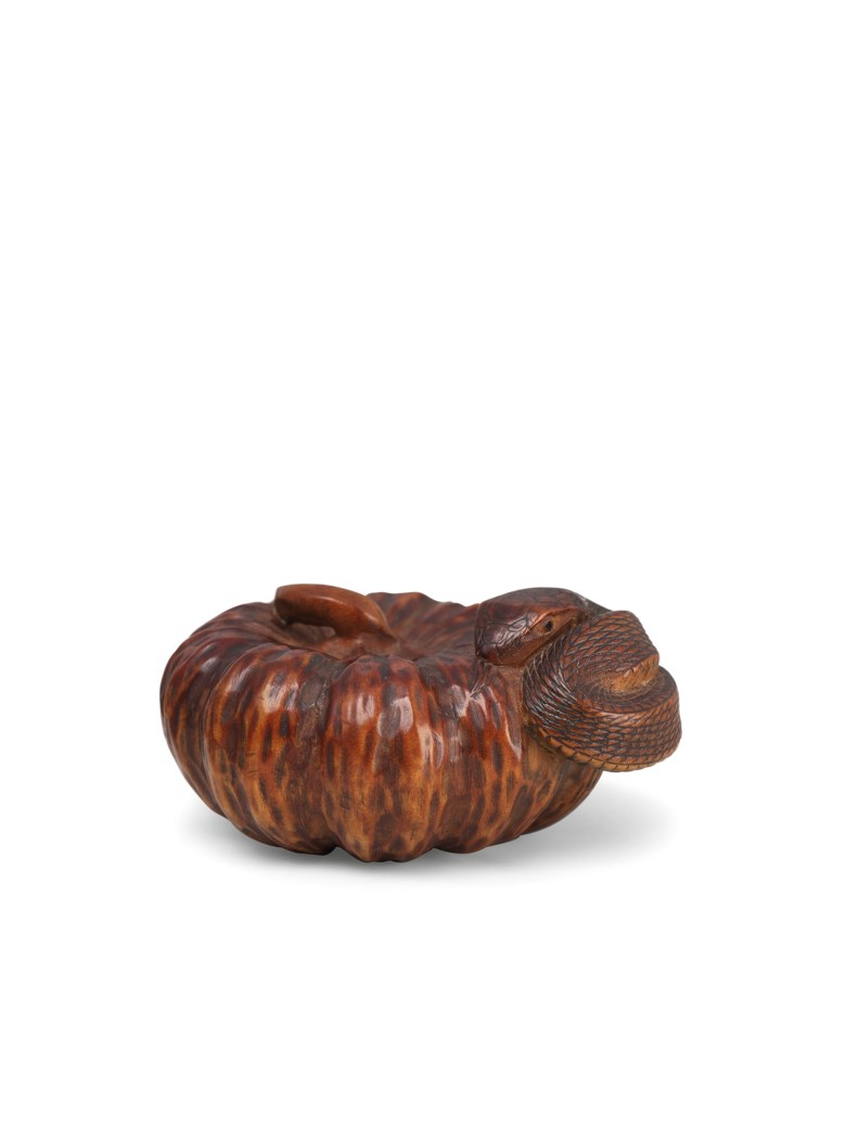 A wood netsuke of a snake and a pumpkin, signed Tadakuni, Edo period (19th century). 4.3 cm long. This lot was offered in Art of Japan on 5 December 2017  at Christie's in London
