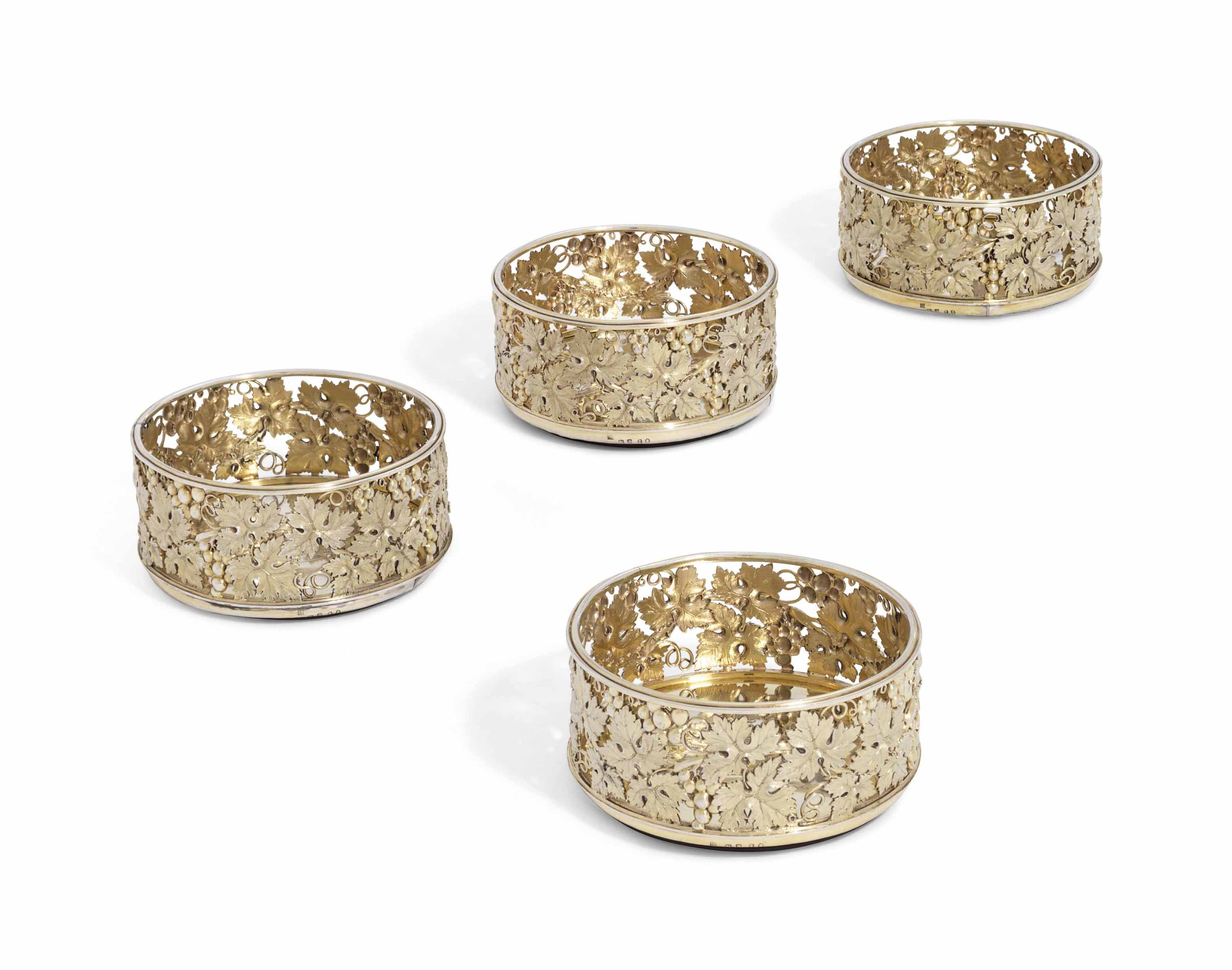 A SET OF FOUR GEORGE III SILVER-GILT WINE-COASTERS