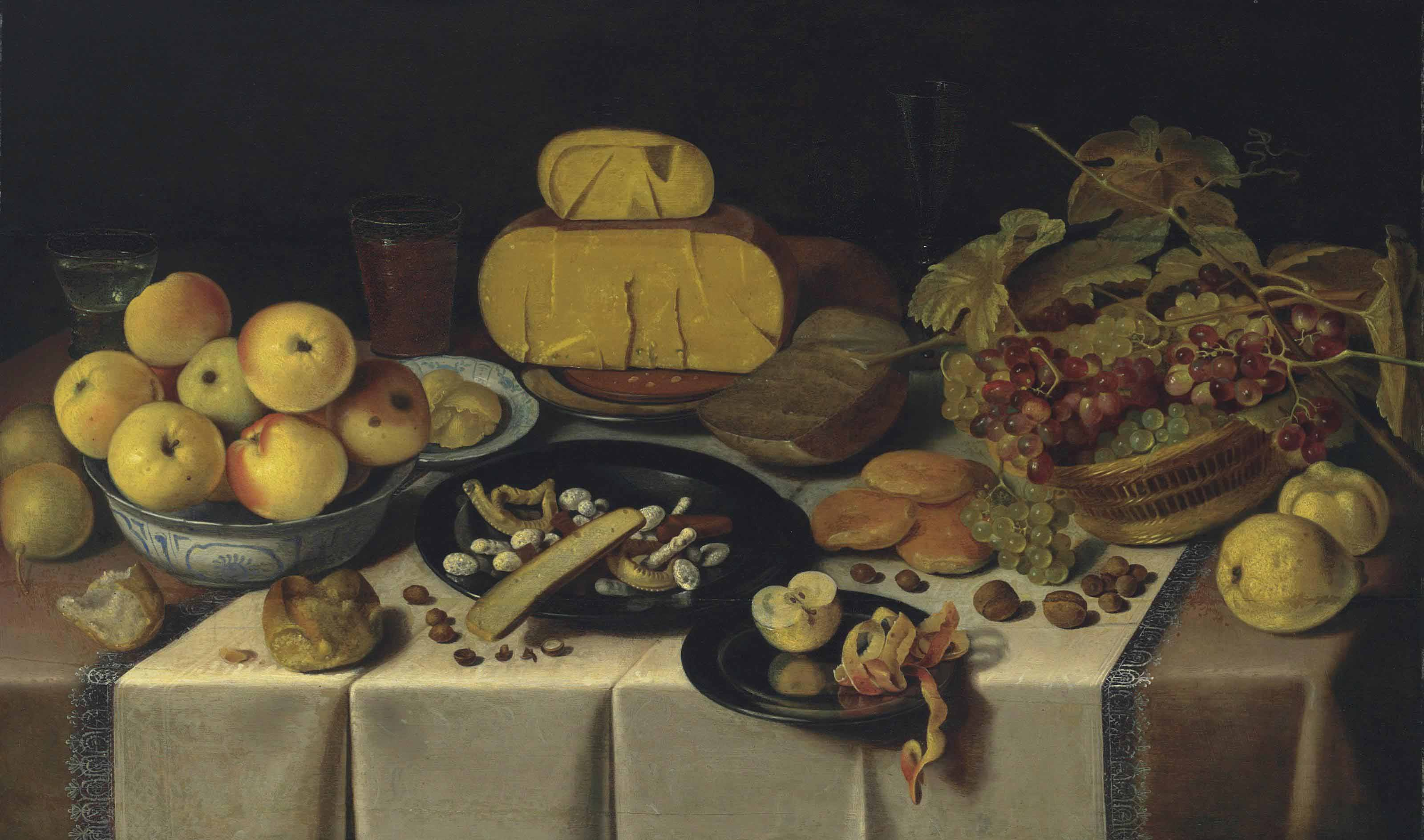 A banquet with cheese and fruit on pewter plates, a basket of grapes, apples in a Wan-Li Kraak porcelain bowl, and bread and glasses on a draped table