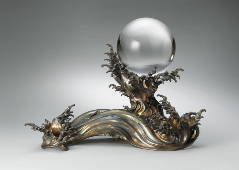 A crystal sphere on a silver wave stand, Meiji period, late 19th century, stand signed Zoroku Zo. 20⅞  in (53  cm) wide, 11¾  in (29.8  cm) high, Japanese wood box. This lot was offered in the Pavilion Sale on 2 October 2017 at Christie's in Hong Kong and sold for HKD 625,000