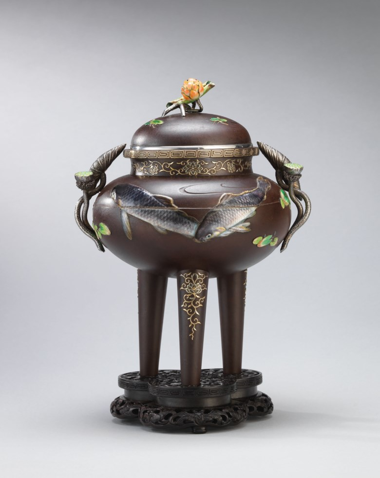 An enamel and soft-metal-inlaid iron incense burner, sealed Koichi Shin (Takasaki Koichi), Meiji period, late 19th century. 8¼  in (21  cm) high, original wood stand, Japanese wood box. Estimate HK$450,000-550,000. This lot is offered in the Pavilion Sale on 2 October 2017  at Christie's in Alexandra House, Hong Kong