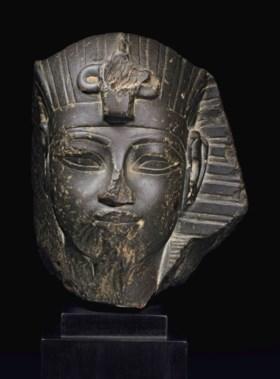 AN EGYPTIAN GREYWACKE PORTRAIT HEAD OF AMENHOTEP III