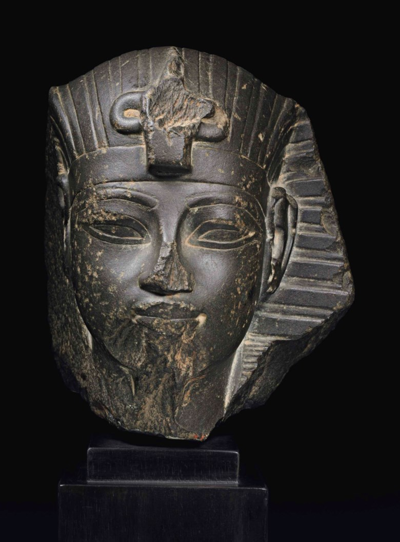 An Egyptian greywacke portrait head of Amenhotep III, New Kingdom, 18th Dynasty, reign of Amenhotep III, 1390-1352 B.C. 6¼  in (15.8  cm) high. Estimate $200,000-300,000. This lot is offered in Antiquities on 25 October 2017  at Christie's in New York
