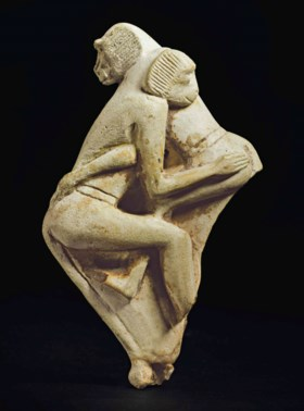 AN EGYPTIAN FAIENCE GROUP OF TWO WRESTLING MONKEYS