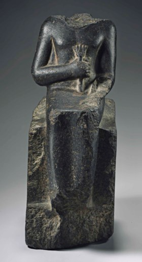 AN EGYPTIAN BLACK GRANITE SEATED SCULPTURE FOR NEITH, OVERSEER OF THE CATTLE OF