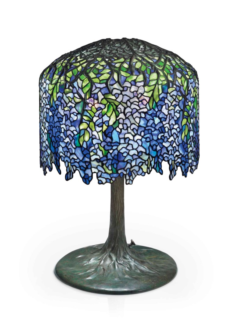 Tiffany Studios, A Wisteria leaded glass and bronze table lamp, circa 1905. 26½  in (68  cm) high, 18  in (45.8  cm) diameter of shade. This lot was offered in the Design sale on 14 December 2017  at Christie's in New York and sold for $492,500