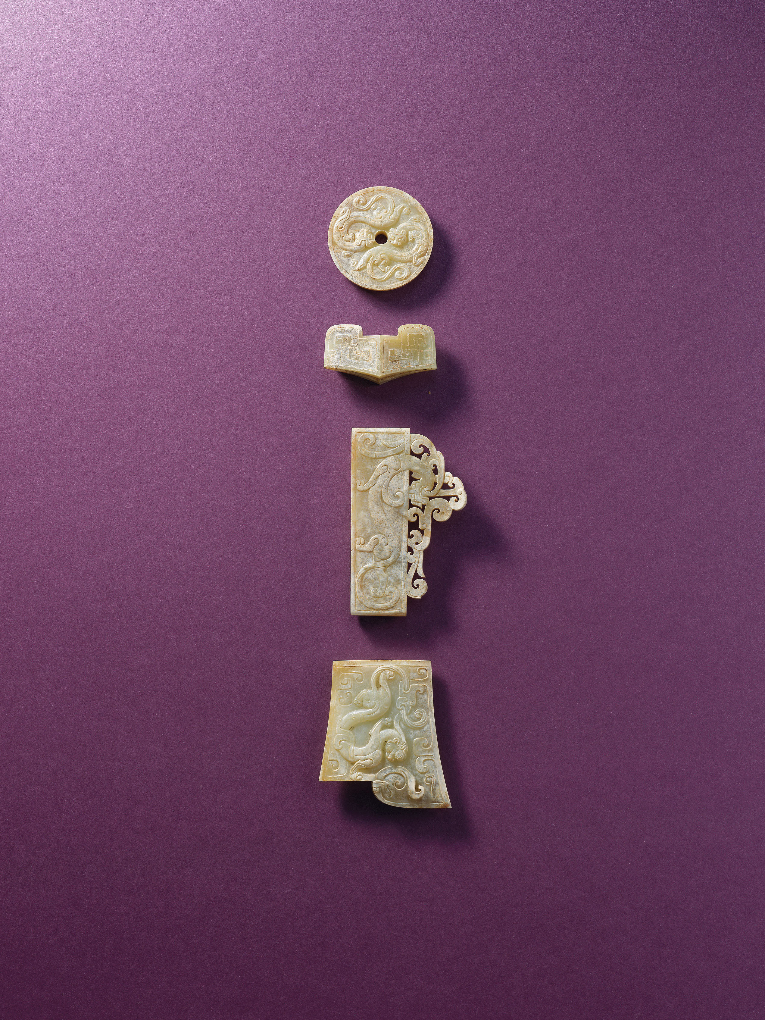 An important SET OF THREE JADE 'CHILONG' SWORDFITTINGS AND A JADE SWORD GUARDWESTERN HAN DYNASTY (206 BC-AD 8)