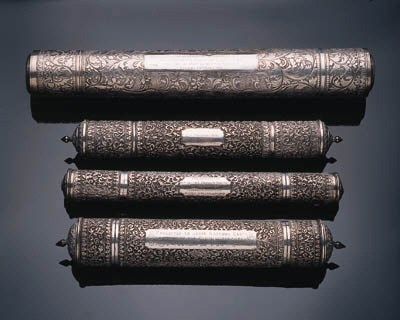 Four silver cylindrical docume