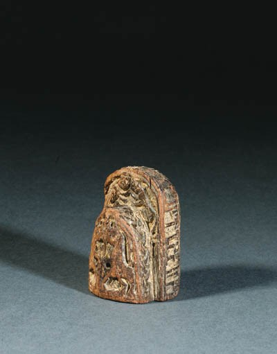 A CARVED WOODEN CHESS PIECE