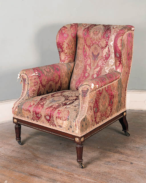 An Edwardian mahogany and parcel gilt wing armchair