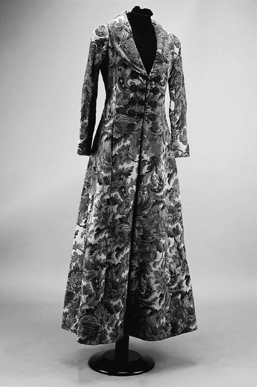 A full-length machine woven tapestry coat, worked with a dense design of scrolling flowers and acanthus leaves, with four frogged fastenings at the front, labelled BIBA, circa 1970