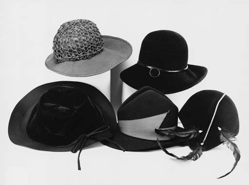 A hat of black felt, with a high peaked crown, the brim with a tuck to one side and applied with an angular red band, labelled JEAN BARTHET PARIS; an asymmetrical cloche hat of black felt, trimmed at one side with three feathers, each with a tear-shaped clear paste at its base and with a string of circular faceted pastes across the crown, labelled DAVID SHILLING; a black felt hat, the high crown with stitched detailing in the form of a cross, trimmed with a band of black plastic embellished with a felt and plastic medallion, the underside of the broad brim also lined in black plastic, labelled FORTNUM AND MASON ORIGINAL DESIGN BY OTTO LUCAS; and two further black hats