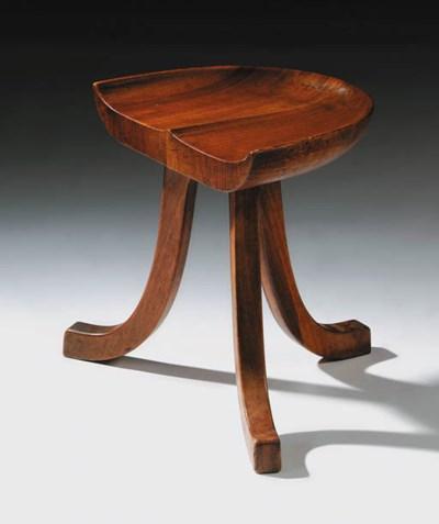 A cherrywood three-legged stoo