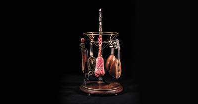 A SET OF MINIATURE MUSICAL INSTRUMENTS AND A CAROUSEL HANGING STAND