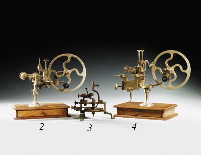 A Swiss mandrel with helical gear drive, the face-plate with three adjustable dogs, compound slide-rest, on cast-iron frame base; and a brass rounding-up or topping tool on mahogany base with fitted draw containing cutters and wheel shoulders  (2)