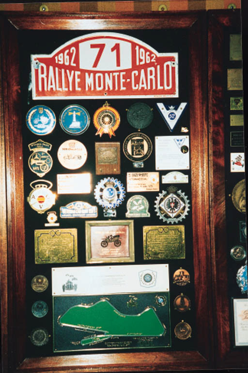 A mounted display collection of commemorative award rally plaques and car badges including Monte Carlo Rally 1962 (No 71); RAC D'Egypte, RAC Italia, ACV, 75 Jahre Deutsche Museum, Munich, ACCV Espagne, Donington, Pioneer Run Medals, Crystal Palace, and many others 1960s-1970s. Approx 30.