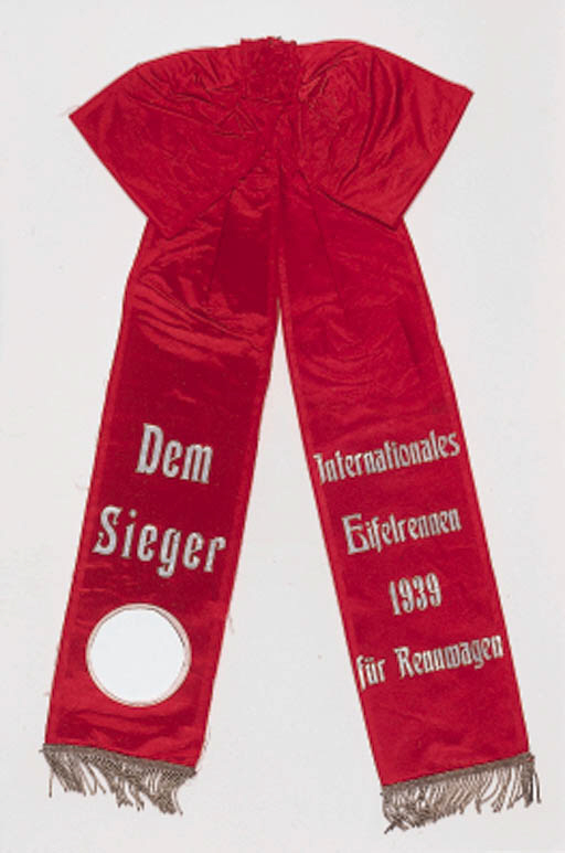 "Eifelrennen - Nurburgring 1939; the winner's sash from the laurel wreath for the event won by Lang in the W154 3-litre car; red silk with gold and silver braided tassels, inscribed in silver lettering ""Dem Sieger - Internationales Eifelrennen 1939 fur Rennwagen,"" mounted on a white ground and framed."