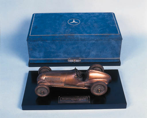 Mercedes-Benz W125 - A fine bronze model of the 1937 Grand Prix 5.6 litre supercharged racing car; cast bronze with excellent detail, mounted upon a black marble base with applied silver engraved inscribed plaque; contained in the original blue suede presentation box with triple-star logo to top.