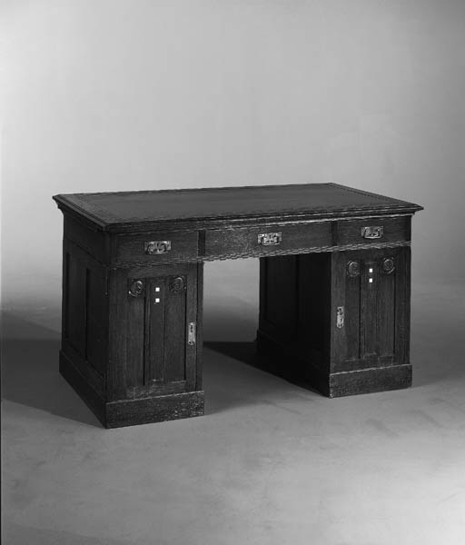 An Arts and Crafts oak and inlaid pedestal desk