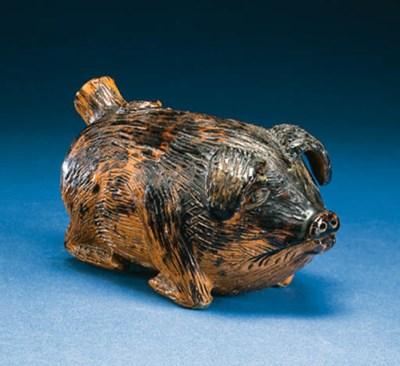 A GLAZED REDWARE PIG RUMMER