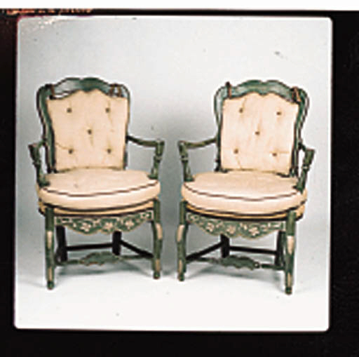 A PAIR OF LOUIS XV PROVINCIAL-STYLE IVORY AND GREEN PAINTED FAUTEUILS Each with a scalloped ladder bacq and outcurved arms around a rosette carved apron and Cabriole legs joined by stretches, upholstered in a beige-colored coarsely woven linen.