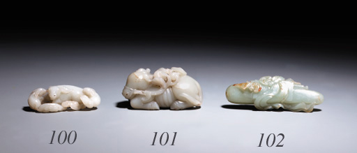 A PALE CELADON JADE MODEL OF A RECLINING MYTHICAL ANIMAL