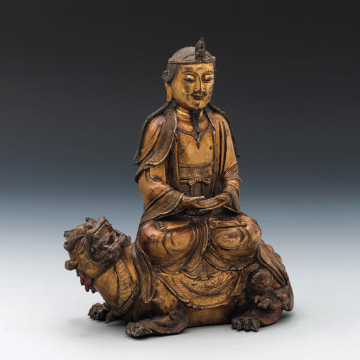 A GILT BRONZE MODEL OF A SEATED FIGURE