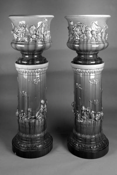 A pair of Continental glazed pottery jardinières and columnar stands