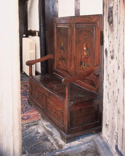 An oak panelled box seat settl