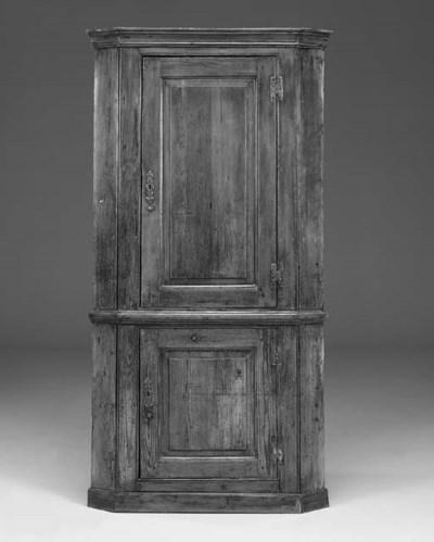 A pine upright corner cupboard