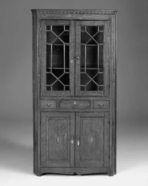 An oak upright corner cupboard