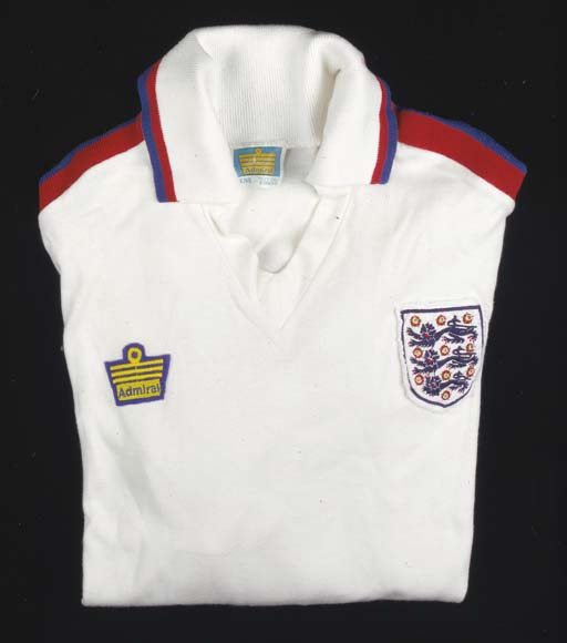 A white, red and blue England International shirt, No.2, with v-neck collar and embroidered cloth badge; and a letter stating that Neal wore the shirt in a match against Wales
