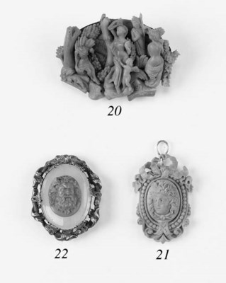 A carved coral pendant set wit