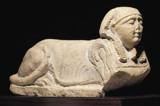 AN EGYPTIAN LIMESTONE SPHINX