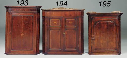 An oak and inlaid corner cupbo