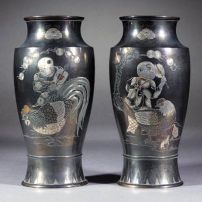 A pair of inlaid bronze taperi
