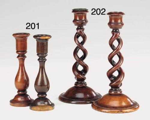 A pair of walnut candlesticks,