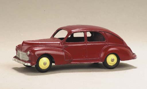 A Dinky cerise 24r Peugeot 203 with cream hubs