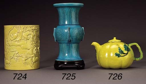 A YELLOW-ENAMELLED CARVED BRUS