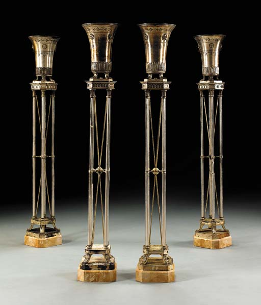 A SET OF FOUR NEOCLASSIC STYLE SILVER-PLATED AND GLASS TORCHERES