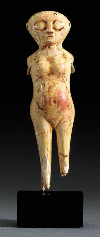 AN EGYPTIAN IVORY FEMALE FIGUR