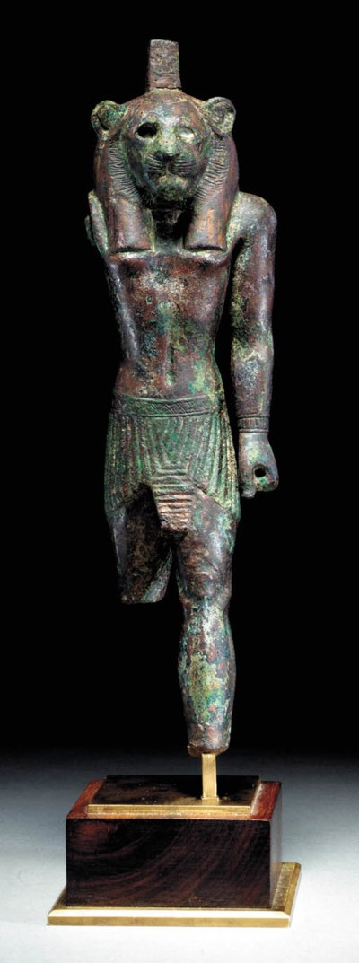 AN EGYPTIAN BRONZE FIGURE OF M
