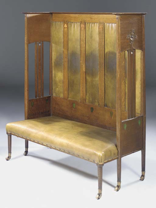 A carved and inlaid oak settle